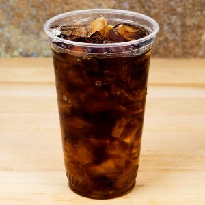 24oz Compostable PLA Cold Cup filled with soda on a wooden table.
