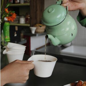 A Kettle Filling a Petite Cup with Tea