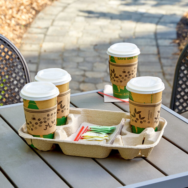 Compostable cups in a cup holder on a wooden table.