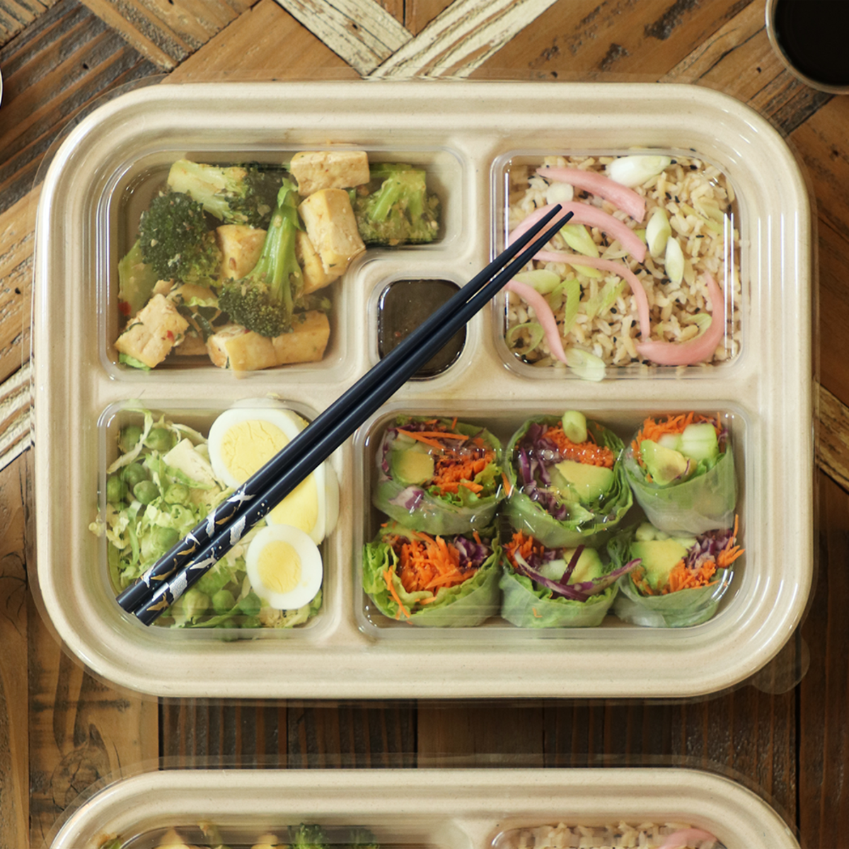 fiber five compartments compostable bento box containing sushi and vegetables.