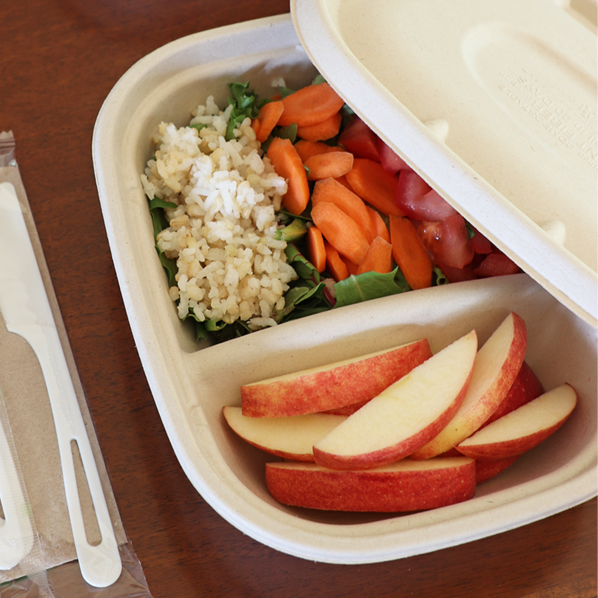 Fiber Food Container Containing Rice, Apples, and Vegetables.